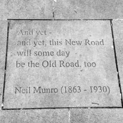 """""""Et pourtant - Et pourtant, cette Nouvelle Route sera un jour la Vieille Route, aussi."""" Citation de Neil Munro gravée sur le sol en face du musée des écrivains à Édimbourg.À propos de la """"nouvelle route"""" reliant Dunkeld à Inverness dans les Highlands dès 1733."""